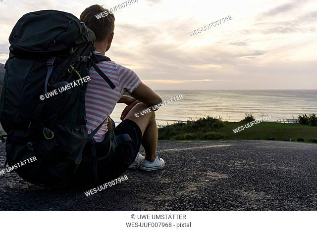 Back view of sitting hiker with backpack looking to the sea