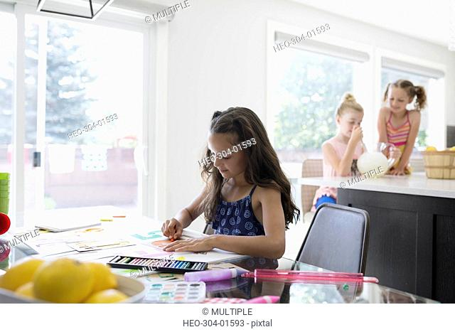 Girl coloring at dining table