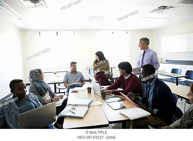 Professor and ESL students talking in classroom