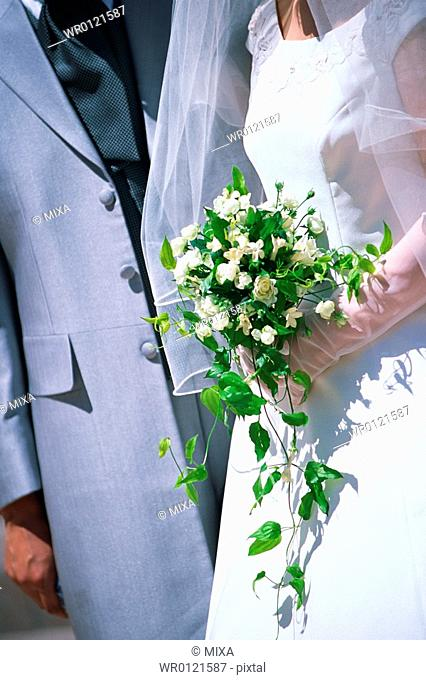 Midsection of bride and groom
