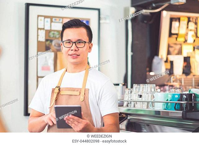 Asian male barista wear apron hold tablet computer coffee menu with smiling face in cafe waiting order from customer ,Coffee business owner concept