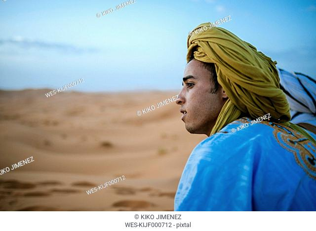 Yound berber sitting in desert, postrait