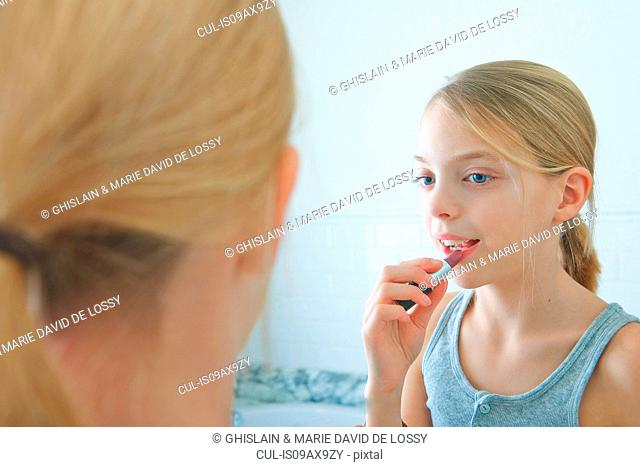 Over the shoulder mirror image of girl applying lipstick