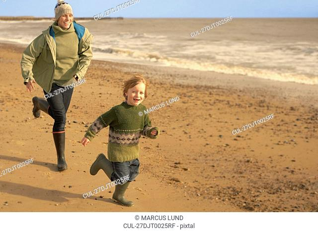 Woman, young boy running on beach. Fall