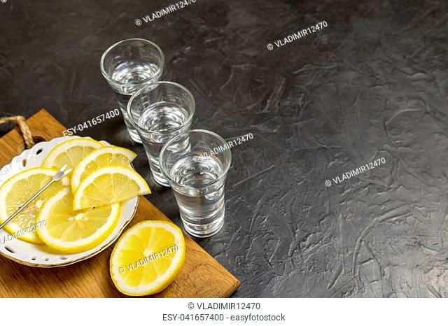 Glass of vodka. And lemon slicing on a plate. Place for your text.,
