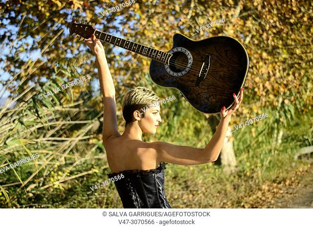 Victoria of Rock and Roll, a woman from Rokera holds her guitar up