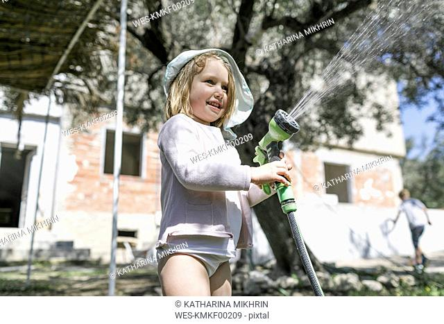 Smiling little girl playing with garden hose