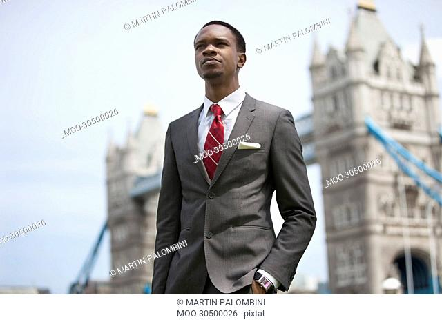 African American businessman standing against London Bridge