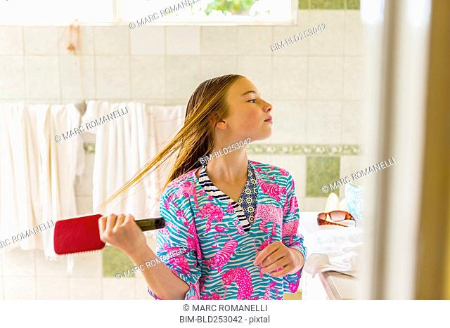 Caucasian girl brushing wet hair in bathroom