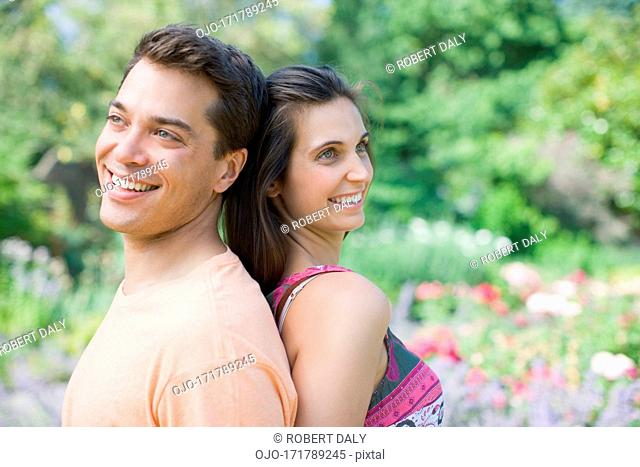 Smiling couple standing back to back in park