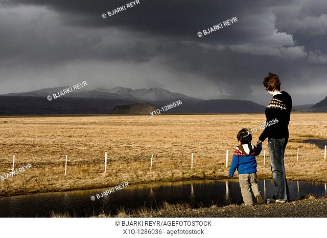 Mother and son looking at Stori-Dimon and Tindfjallajokull glacier, South Iceland