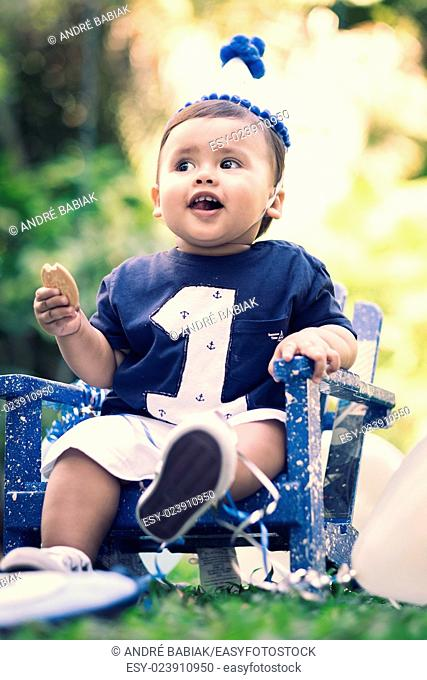 Male hispanic child at his first birthday garden party