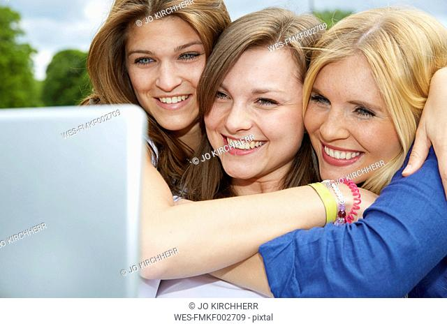 Three smiling friends taking selfie with tablet