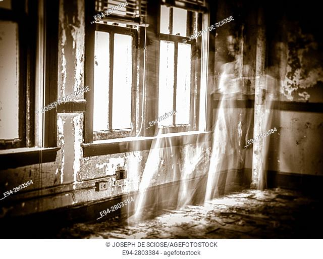 A ghostly figure of a woman in a white dress moving a room in an abandoned building