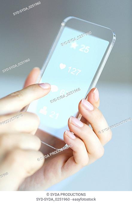 hands with social media icons on smartphone