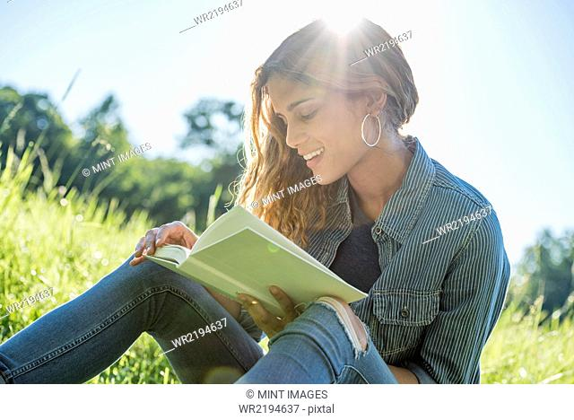 A young woman sitting in the sun reading a book