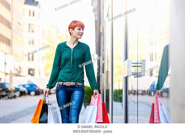 Smiling young woman holding shopping bags looking at shop window
