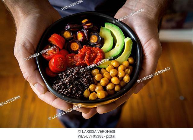 Man's hands holding Buddha bowl of amaranth, avocado, Purple Haze, roasted chickpeas, tomatoes, ajvar