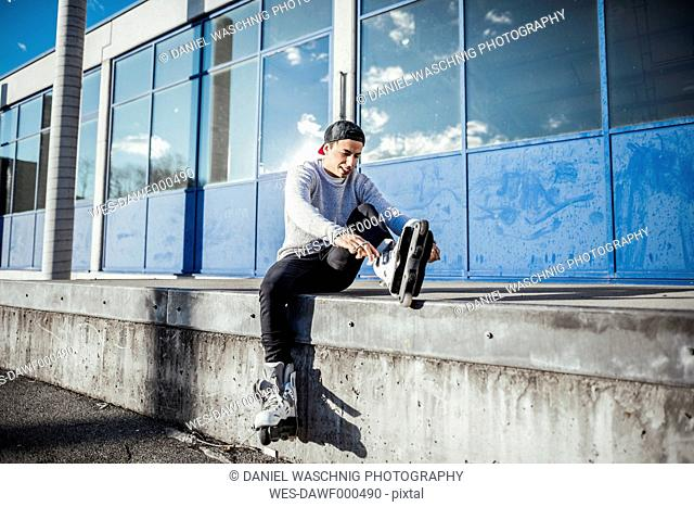 Young man sitting on ramp putting on inline skates