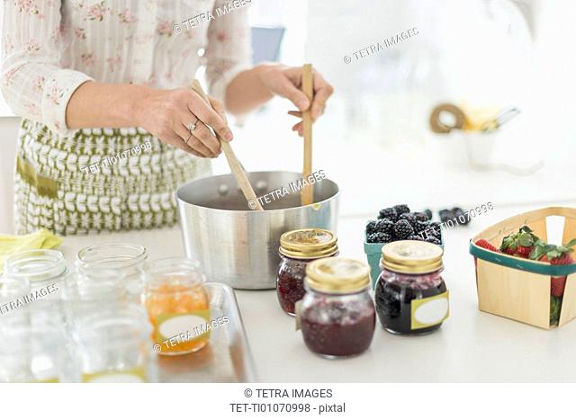 Midsection of woman making preserves in kitchen