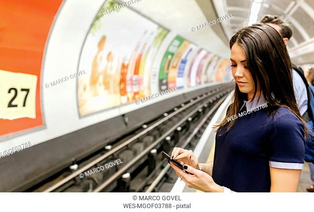 UK, London, young woman waiting at underground station platform looking at cell phone