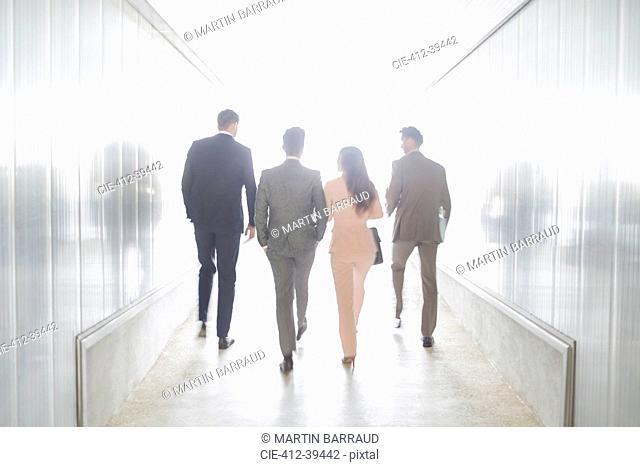 Business people walking in illuminated office corridor