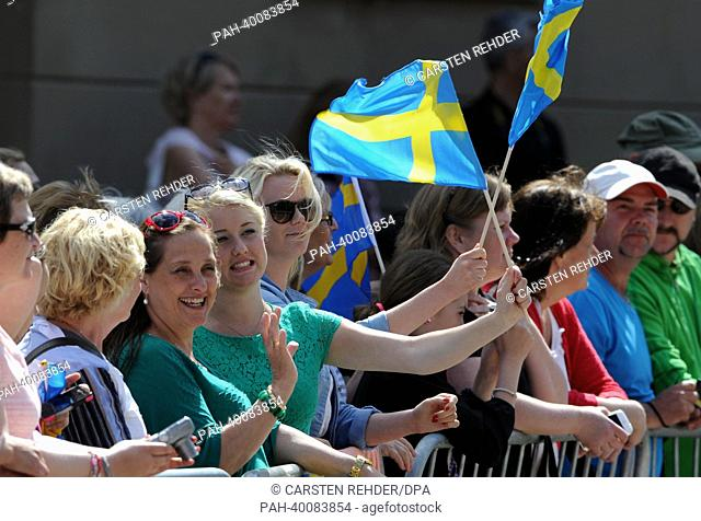 Fans wave with Swedish flags outside the Royal Palace waiting for the Royal Wedding of Swedish Princess Madeleine and her husband Chris O'Neill in Stockholm
