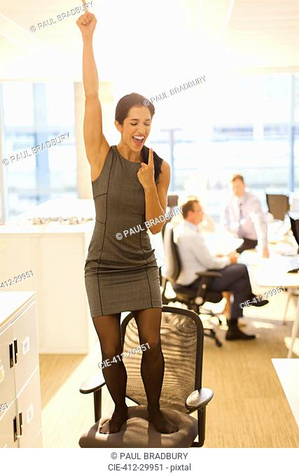 Exuberant businesswoman celebrating on top of office chair