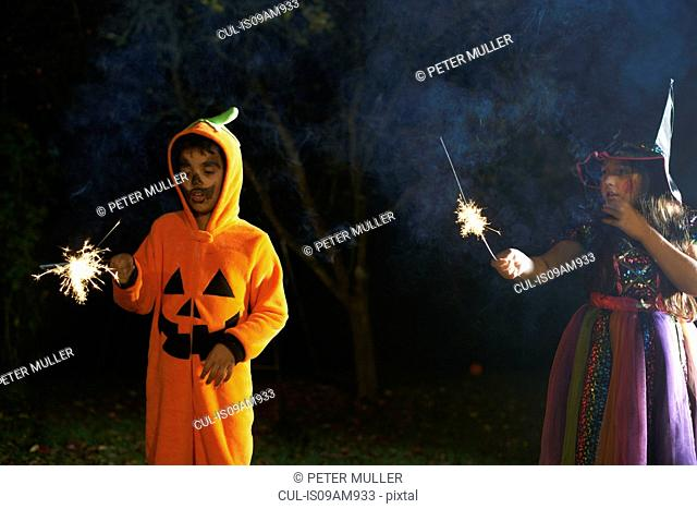 Brother and sister wearing halloween costumes holding sparklers in garden at night