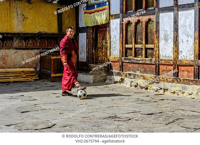 Monk playing football at the monastery in Bhutan