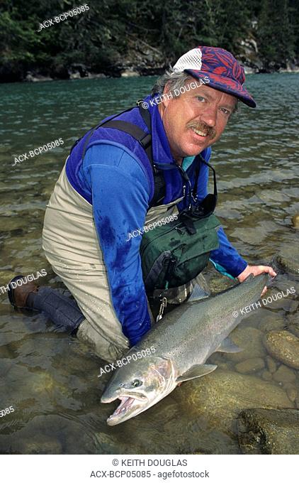 Angler holding steelhead, Dean river, British Columbia, Canada