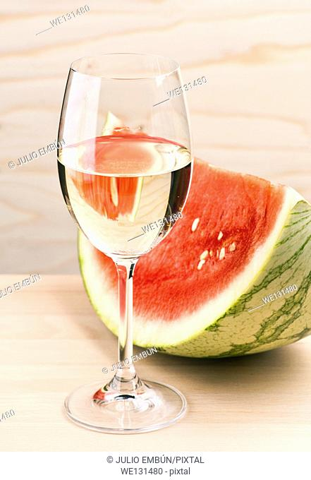 cup serving of watermelon with white wine, on wood base