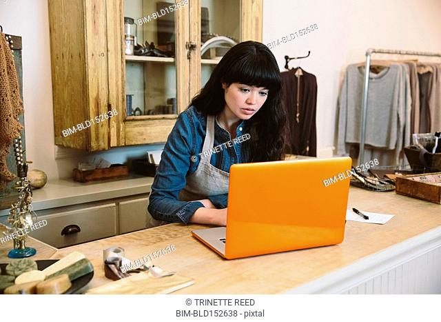 Mixed race employee using laptop in store