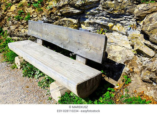Wooden bench made of tree trunks is placed on the tourist trail