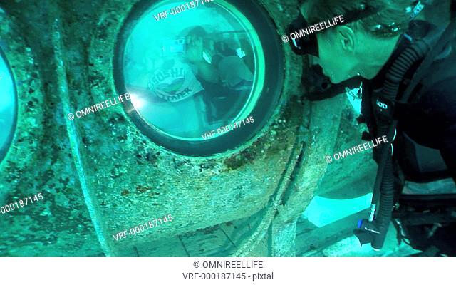 Teenage female taking photograph with digital camera through submarine window of scuba diver