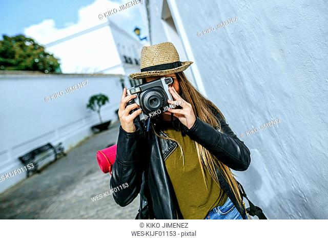Young traveling woman taking photos in a town