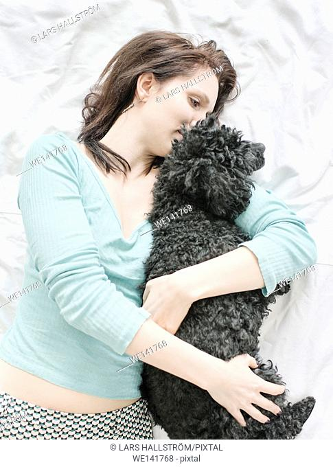 Woman lying in bed hugging black poodle. Lifestyle image showing affection and the bond between dog and human