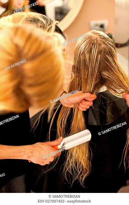 Hair stylist at work - hairdresser combing hair to the customer before doing hairstyle in a professional salon
