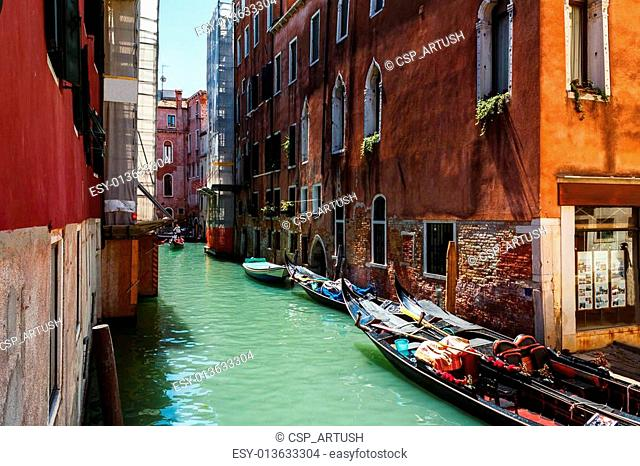 Venice canal with boats and gondolier