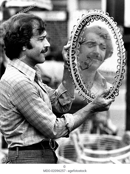 Italian actor Orso Maria Guerrini looking his own face in a mirror at the flea market. Rome, 1970s