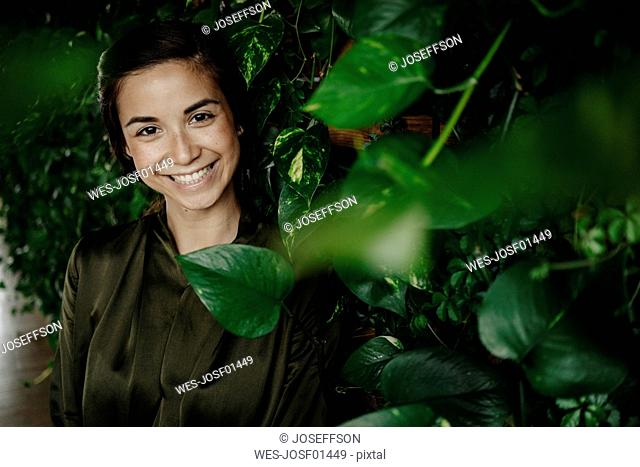 Portait of smiling young woman at wall with climbing plants
