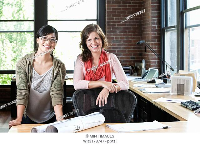 Asian woman and Caucasian woman at a workstation in a creative office