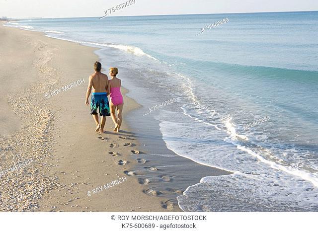 Walking on deserted beach arm in arm