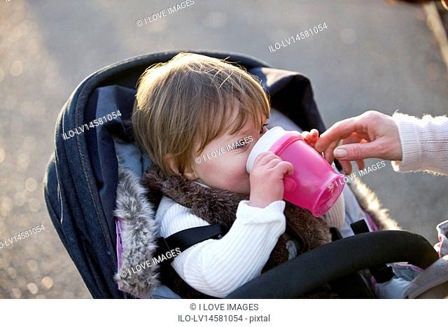 A baby girl drinking from a cup in her stroller