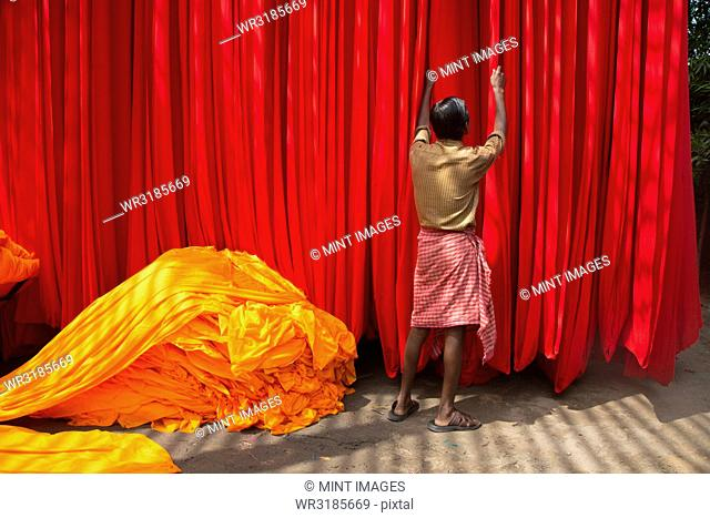 Rear view of man hanging up vibrant and bright red fabric, heap of orange fabric on floor