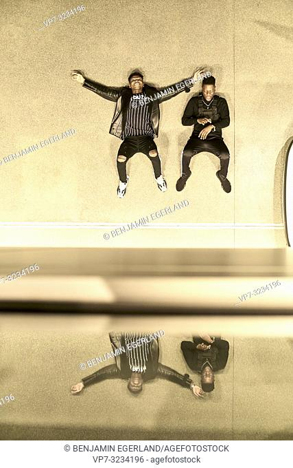 best male friends laying together on floor, mirrored