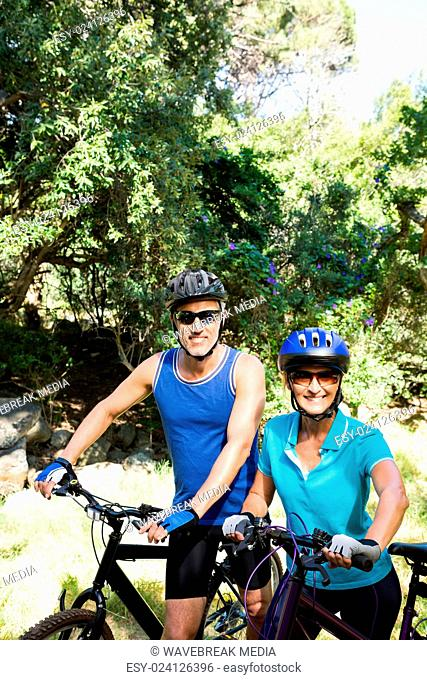 Mature couple with sunglasses posing with their bikes
