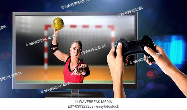 Hands holding gaming controller with handball player on television
