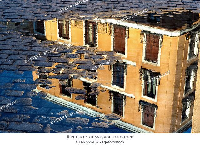 Apartments buildings reflected in a puddle in the Plaza de la Villa, Madrid de los Austrias, central Madrid, Spain