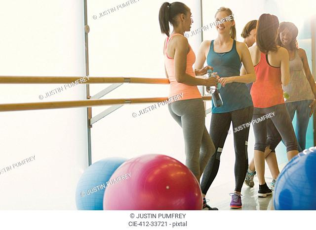 Smiling women talking and drinking water at barre in exercise class gym studio